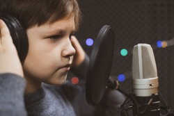 Boy in headphone is singing or talking into microphone with pop filter in voice recording studio. Young singer recording his voice for phonogram performance for entertainment.