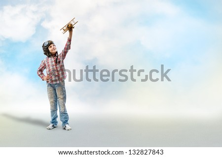 Boy in helmet pilot playing with a toy wooden airplane in the clouds dreaming of becoming a pilot