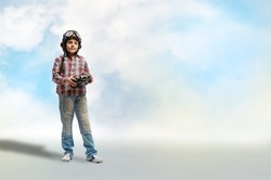 Boy in helmet pilot radio remote control with the game