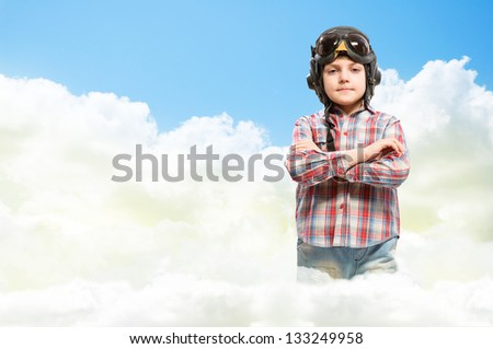 Boy in helmet pilot stands with his arms crossed in the clouds, dreaming of becoming a pilot