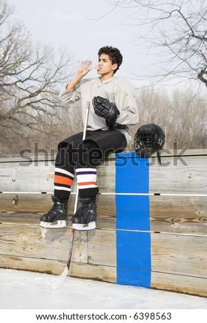 Boy in ice hockey uniform holding hockey stick sitting on sidelines drinking water.