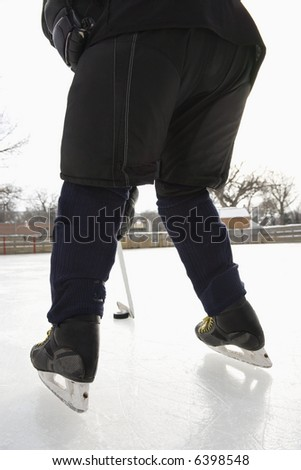 Boy in ice hockey uniform skating on ice rink moving puck.