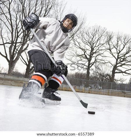Boy In Ice Hockey Uniform Skating On Ice Rink Moving Puck. Stock ...