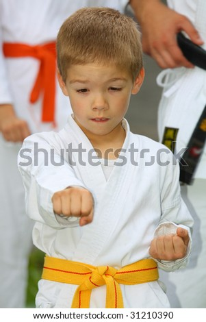 boy in karate suit with yellow belt training