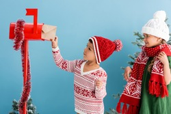 boy in knitted sweater and hat putting envelope in mailbox near sister in winter outfit isolated on blue