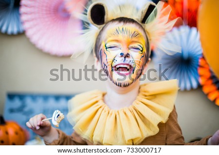 Boy in lion fancy dress laughing at children's halloween party Stock photo ©