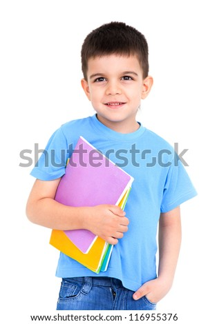 boy in primary school with notebooks poses at white wall