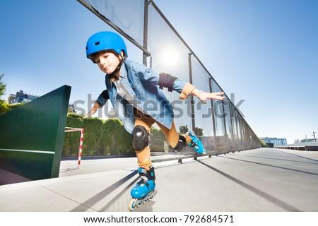Boy in roller blades doing tricks at skate park #792684571