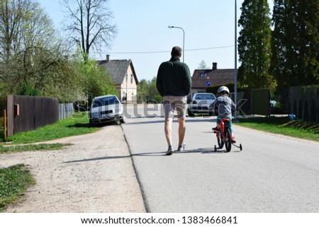 Boy in safety helmet cicling first bike on road in spring day, father learning little son to ride with bicycle on street, back view. Happy child making sports. Active leisure activities for children.  #1383466841