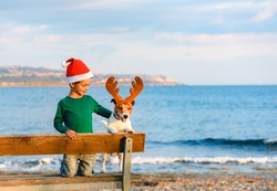 Boy in Santa Claus hat and dog in costume of Rudolph reindeer at winter beach in South Europe
