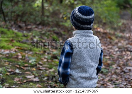 Boy in shirt, vest, and knitted hat outdoors.  Cool sunny day.  View from the back;  medium shot. #1214909869