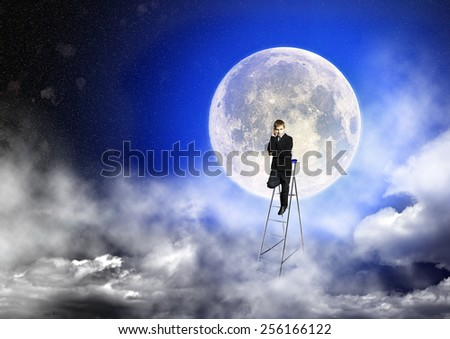 Boy in suit stands on a step-ladder against the background of a full moon and a starry sky