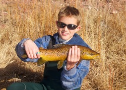 Boy in sunglasses holding a large Brown Trout he caught on a dry fly, fly fishing