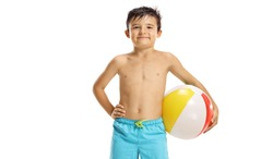Boy in swimming shorts holding a beach ball isolated on white background