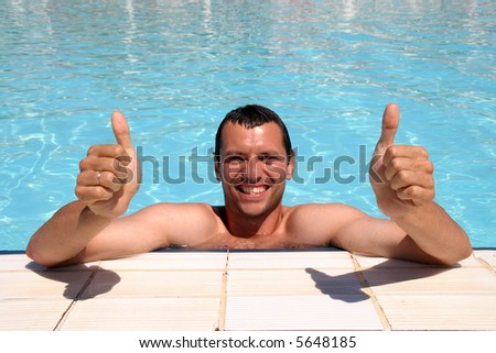 boy in swimmingpool with thumbs up - stock photo