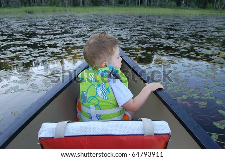 Boy in the bow of a canoe searches the lily pads for frogs/Look for Adventure/Take time to look around and find new treasures