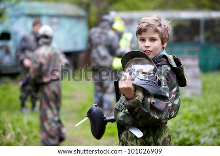 Boy in the camouflage holds a paintball gun barrel up in one hand and protective helmet in another, standing halfturned on the paintball ground with group of players on the background.