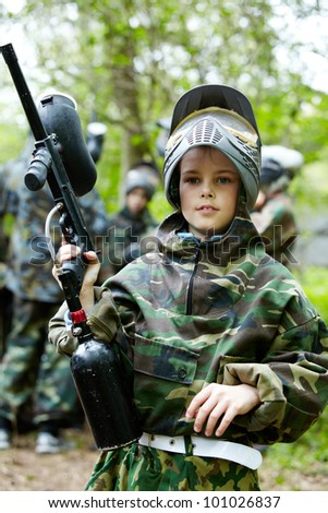Boy in the camouflage suit holds a paintball gun barrel up , standing on the paintball ground with group of players on the background.