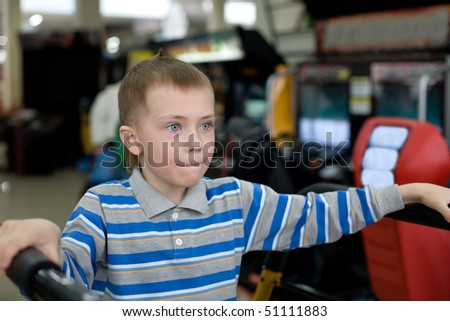 Boy in the children's amusement arcade. Playing a video game. - stock photo