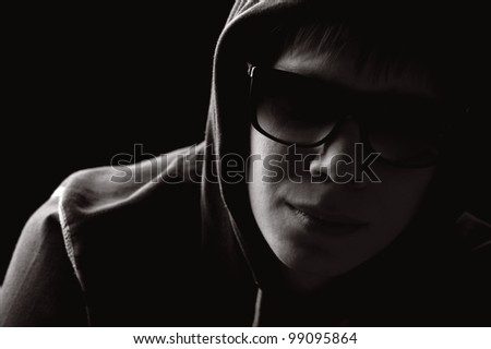 boy in the hood and sunglasses looking into the camera