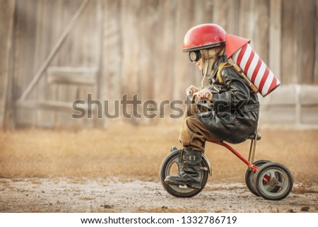 Boy in the image of a rider and a rocketman play in the backyard of the house