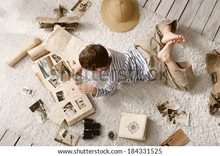Boy in the image traveler studying his book of travel and adventure in her room - Shutterstock ID 184331525