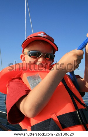 Boy in the orange life jacket with sunglasses on the yacht. He is pulling sheets (ropes). Work aboard, sailing.