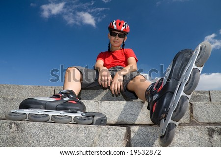 boy in the rollerblades, sitting on stairs