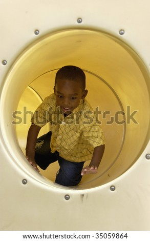 boy in tube on playground