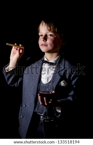 boy in tuxedo, with glass of red wine and a cigar