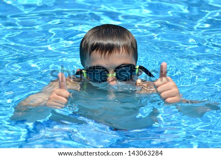 boy in water with thumbs up summer concept