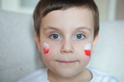 boy in white shirt with polish flag on his cheeks