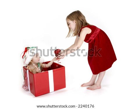 Boy in xmas box and his big sister is giving him a small gift