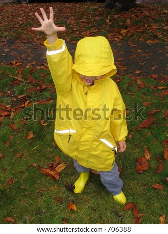 Boy in yellow raincoat and boots holding his hand up with five fingers spread in rain indicating number five