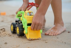 Boy in yellow swimming trunks playing with an excavator and a bulldozer near the sea on a sandy beach
