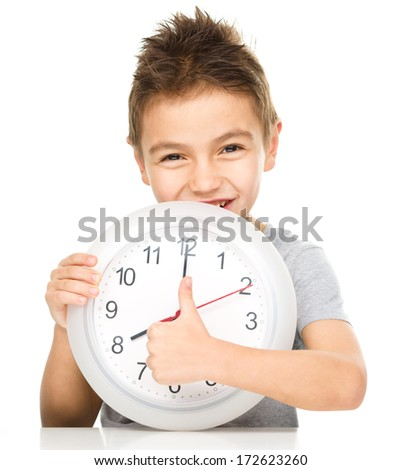 Boy is holding big clock and showing thumb up sign, isolated over white