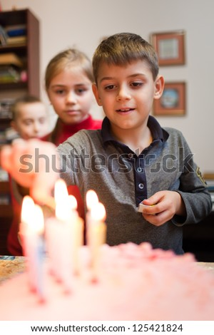 Boy is lighting the birthday cake candles