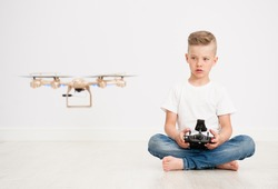Boy is operating the drone by remote control.