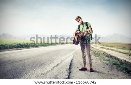 Boy is playing a guitar while he is hitchhiking