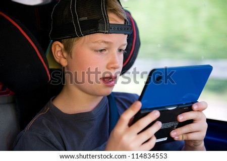 boy is playing electronic-game in the car