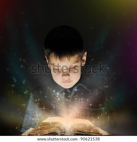 Boy is reading a magic book in the dark on a black background