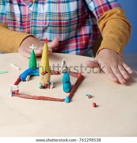 Boy is sculpting with colorful modelling clay. Close up.  #761298538