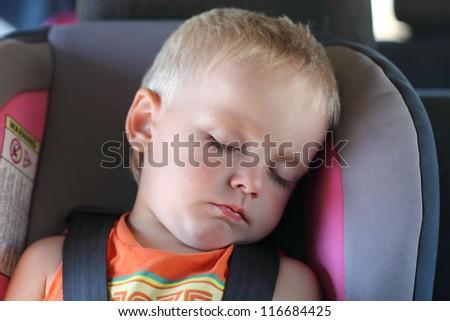 Boy is sleeping in a child car seat