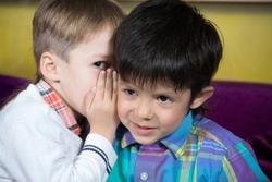 Boy is telling a secret to a friend