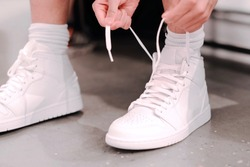 Boy is trying brand new white sport shoes. Sitting on the couch and tied shoelaces. Student back to school, shopping, gift and fashion concept.