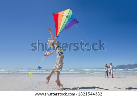 Boy jumping and reaching for kite on sunny beach