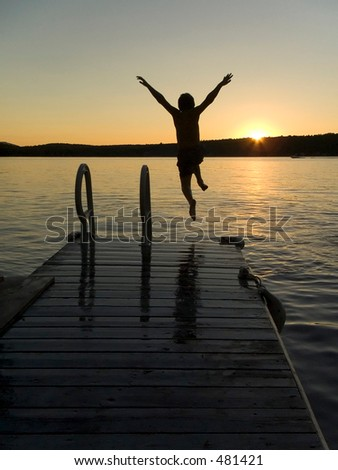 Boy jumping in a lake during sunset