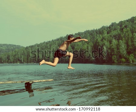 boy jumping in lake at summer...