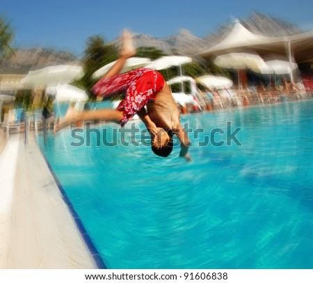 boy jumping into blue swimming pool in resort