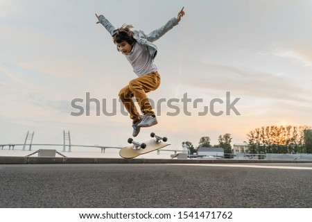Photo of  Boy jumping on skateboard at the street. Funny kid skater practicing ollie on skateboard at sunset.